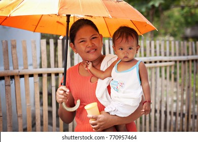 PHILIPPINES - June, 2013: Smiling Filipino woman with a child on her hands, Philippines. Filipino people portrait.