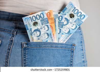 Philippines Peso in a female jeans pocket. Philippine pesos notes stuck in a woman jeans pocket. Pesos in a girl's denim pants buttock pocket. Money in jeans pocket