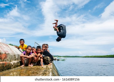 PHILIPPINES, SIARGAO - MAY 20, 2018: Children pose on camera while they play and have fun bathing in the sea of the port of El Carmen
