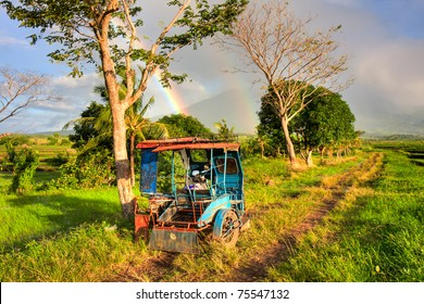 A Philippines tricycle parked in the middle of a rice field with a beautiful rainbow in the background.