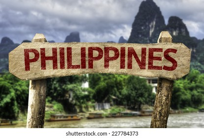 Philippines wooden sign with a rural background