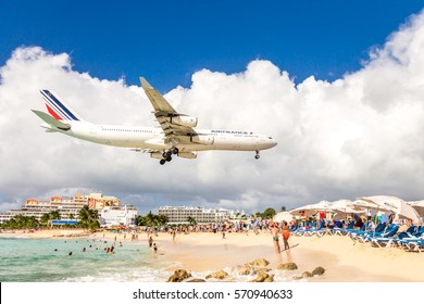 PHILIPSBURG, SINT MAARTEN - DECEMBER 13, 2016: A commercial airplane approaches Princess Juliana airport above onlooking spectators on Maho beach.