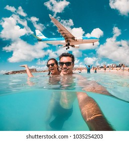 Philipsburg, Sint Maarten - Feb 16, 2018: Couple of tourists observe low flying airplanes landing near Maho Beach on island of Sint Maarten (Saint Martin) in the Caribbean.