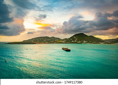 Philipsburg, Sint Maarten. Sunset ocean view in the Caribbean with cruise ship fuel bunker vessel sailing to coast. Mountains stretch along the coastline landscape with endless water all around.
