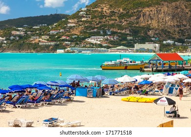PHILIPSBURG, ST. MAARTEN - JAN.19: Tourists on Great Bay Beach in St. Maarten on Jan. 19, 2011. The beach was refreshed with new sand, dredged from the harbor to allow for larger cruise ships.
