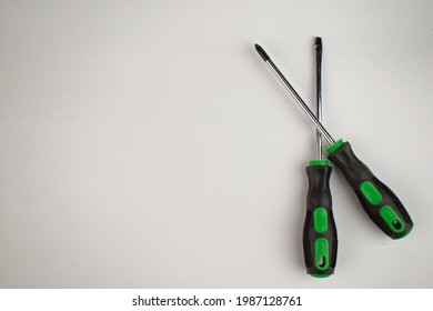 Phillips and flathead screwdrivers lie together. Black rubber handle with green plastic. Isolate. Copy space. Flat lay.