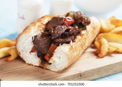 Philly beef steak sandwich with french fries on wooden board