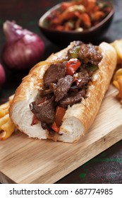 Philly steak sandwich with french fries served on wooden board