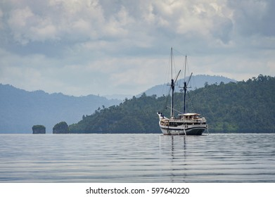 Phinisi Schooner Anchored in Raja Ampat, Indonesia. A traditional phinisi schooner sails the waters off Waigeo Island taking passengers to remote spots in the Indonesian archipelago.