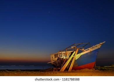 Phinisi wooden boat is under repair, taken during a blue hours with a background of the sky and star points