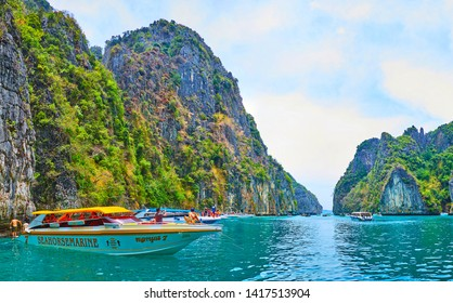 PHIPHI LEH, THAILAND - APRIL 27, 2019: The line of tourist boats at the cliffs of Phi Phi Leh Island; the tourists enjoy clear waters of Pileh Bay, on April 27 in PhiPhi Leh