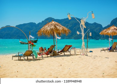 PHI-PHI, THAILAND - FEB 09, 2015:  People relax on sandy beach Phi-Phi Islandsin February 2015. Despite holiday season, there is still not very crowded places on beach