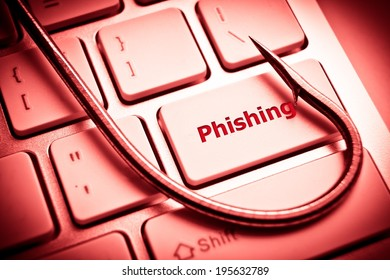 phishing / a fish hook on computer keyboard / computer crime / data theft / cyber crime