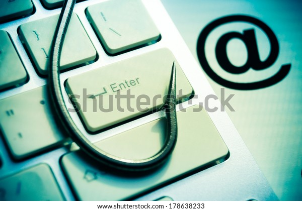 phishing / a fish hook on computer keyboard with email sign / computer crime / data theft / cyber crime