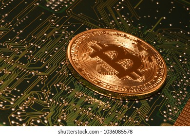 phisical bitcoin over electronic circuit board.