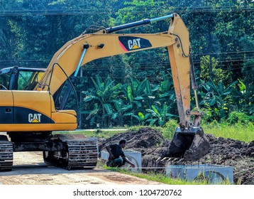 phitsanulok city,Thailand ; Oct 11,2018 ;Under construction and repair roads.Public drains are placed by construction workers.Digger driver controlling loader backhoe at phitsanulok province,Thailand.