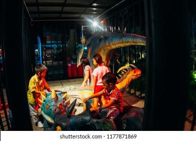 Phitsanulok / Thailand - 6152018: Thai children playing dinosaur robot in amusement park