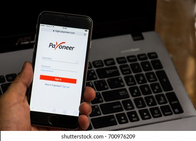 Phitsanulok Thailand - August 19,2017 Using Payoneer on iPhone with laptop background. Payoneer is a worldwide online payment system