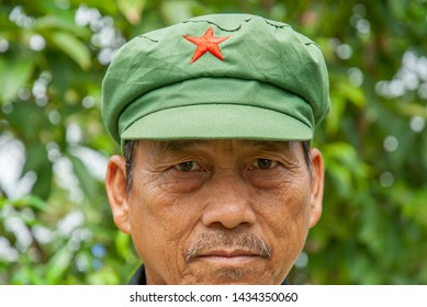 Phitsanulok, Thailand - AUGUST 26, 2017: Portrait shot of Hmong tribe senior man wearing a Mao style cap standing in green forest blurred background. Phu Hin Rong Kla National Park.