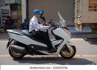 PHITSANULOK, THAILAND - OCTOBER 27, 2018:  Photographer on white  Motorcycle   in Phitsanulok province, Thailand