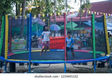 PHITSANULOK, THAILAND - OCTOBER 27, 2018: Boy and girls playing on the outdoor trampoline in Phitsanulok province, Thailand