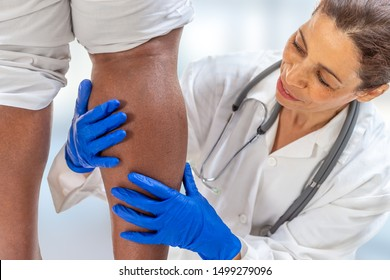phlebologist inspecting a woman's leg looking for varicose veins on a white background