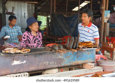 PHNOM KULEN, CAMBODIA - FEB 15, 2015 - Woman selling smoked fish  at the market in Phnom Kulen, Cambodia