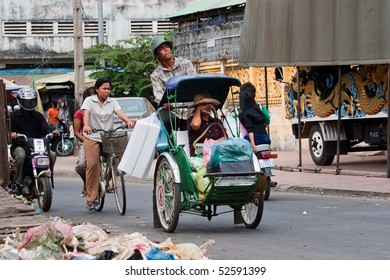 PHNOM PEHN, CAMBODIA - JANUARY 2: A cyclo driver peddling his passenger/customer and her shopping on January 2, 2008 in Phnom Pehn, Cambodia..