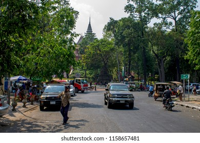 Phnom Penh, Cambodia - 02.16.2018: Bustling city life in the streets below Wat Phnom including traffic, a man on his mobile phone crossing the road, street vendors and the tower of Wat Phnom.