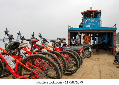 Phnom Penh, Cambodia - 02.17.2018: Red mountain bikes and motorcycles lined up on a ferry crossing the Mekong River.