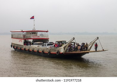 Phnom Penh, Cambodia - 02.17.2018: A vehicle ferry filled with cars, motorbikes and people crosses the Mekong River in Phnom Penh, Cambodia.