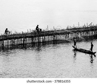 PHNOM PENH, CAMBODIA, 18 JULY 2010: Silhouettes of wooden jetty, tourists riding a bicycle and fisherman with net  row a boat.