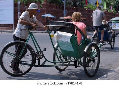 PHNOM PENH, CAMBODIA, 2014: A male Cyclo driver peddling his passenger/customer and her shopping in Phnom Penh, Cambodia.
