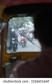 Phnom Penh, Cambodia - April 27 2019: Traffic along the streets through a tuc tuc window. Day time.