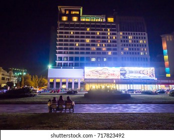 Phnom Penh, Cambodia - Dec 26, 2016 : 3 girls are watching a huge monitor from Nagaworld hotel in the little park in front of the building. This building is also the biggest Casino among that area.