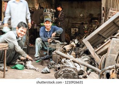 Phnom Penh, Cambodia - December 21,2016: Cambodian young males mechanics repairing engine in their street workshop near Phnom Penh Old market.
