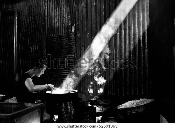 PHNOM PENH, CAMBODIA - DECEMBER 25:  A black and white photo of a Cambodian woman cooking in the Russian market December 25, 2007  in Phnom Penh, Cambodia.