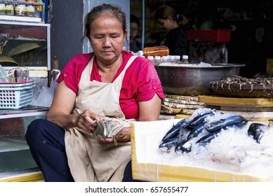Phnom Penh, Cambodia - December 30, 2016: An unidentified woman check the day's earnings at the Central Market of the Cambodia capital.