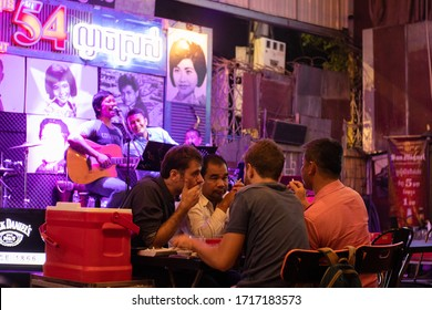 Phnom Penh, Cambodia, February 2020: Group of four mixed people, two khmer locals and two foreigners, at a restaurant having dinner, drinking beer and enjoying live music. Musicians behind. Phnom Penh