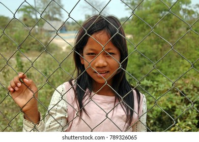 Phnom Penh, Cambodia - February 21, 2008; Young Girl Begging for Money outside the fence at the Cambodian Killing Fields.
