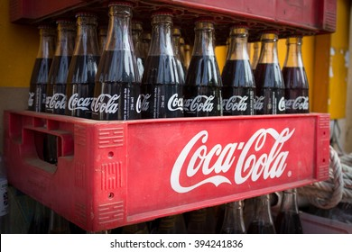 Phnom Penh, Cambodia- January 02, 2014: Coca Cola bottles in red plastic box, vintage style. Coca cola is probably the worlds most famous brand.
