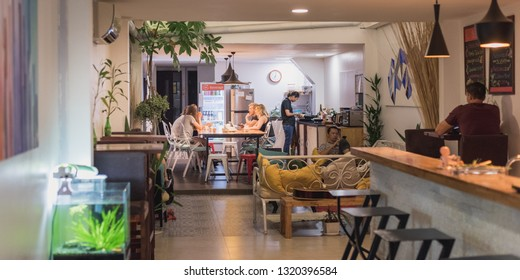 Phnom Penh, Cambodia - January 13, 2019: an interior of Sla Boutique Hostel, its bar, the common area and kitchen, with several customers in it.