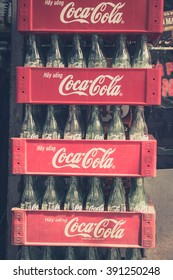 Phnom Penh, Cambodia, January 17, 2014: Empty bottles of Coca Cola in red plastic box.Coca-Cola is probably the worlds most known brand.(vintage style filtered)
