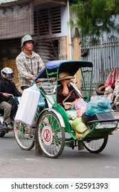 PHNOM PENH, CAMBODIA - JANUARY 2: A male Cyclo driver peddling his passenger/customer and her shopping on January 2, 2008 in Phnom Penh, Cambodia.