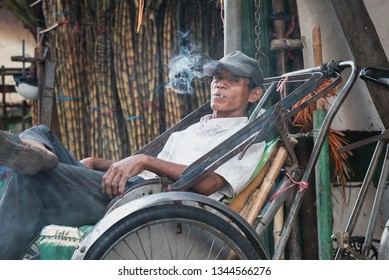 Phnom Penh, Cambodia - January 28, 2019: a cycle rickshaw driver smokes a cigarette resting in his cyclo in the street.