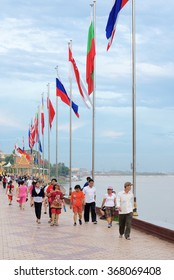 PHNOM PENH, CAMBODIA - JULY 3, 2014: Unidentified Asian people walk along Tonle Sap River in the downtown near the Royal Palace.