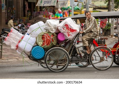 PHNOM PENH, CAMBODIA - MARCH 21: Plastic ware vendor driving his bicycle in Phnom Penh, Cambodia on March 21, 2014