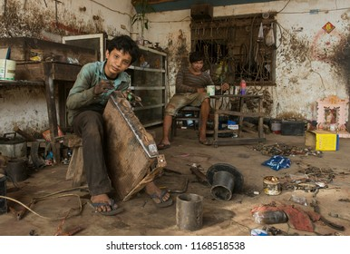 PHNOM PENH, CAMBODIA - MAY 2, 2014: Young Cambodian boys in a mechanical workshop. Children are used as cheap labourers through out Asia.