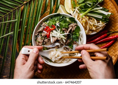 Pho Bo Soup with beef and chopsticks in male hands close-up