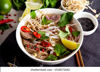 Pho Bo - Vietnamese fresh rice noodle soup with beef, herbs and chili. Vietnam's national dish. Top view